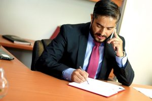 lawyer writing while talking to someone in the phone